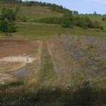 Le réservoir vide d'eau, bien en herbe où les vaches viennent paître